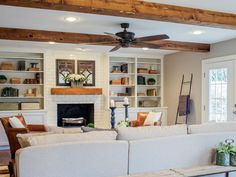 white-painted brick fireplace wall w/ built-in shelves/cupboards & hearth w/ wood mantel shelf & beams