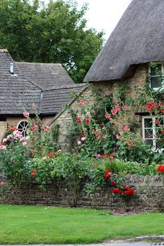 A clever English cottage garden near Barnsley House in Gloucestershire, England. These tall growing boxes made from stone are brilliant and add vertical interest to the garden. Vine-type plants bring character and a free hanging feel. www.ModernCrowd.com More