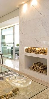 Lareira revestida em marmore pigues e iluminação pontual, projeto da arquiteta Fernanda Marques.
