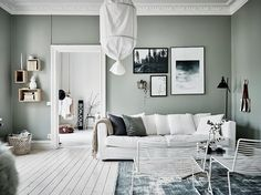 I like the vibe of this home. The green-grey walls combined with the white hard wood flooring give the home a very fresh look and the furniture and accessories are chosen very carefully to create a st