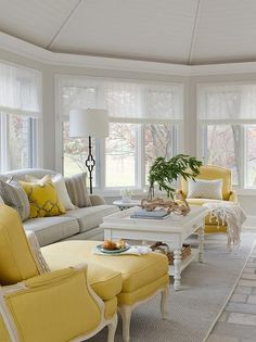 Yellow and gray sunroom features a gray roll arm sofa illuminated by Suzanne Kasler Quatrefoil Floor Lamps in Bronze facing a white turned leg coffee table flanked by yellow bergere chairs atop a gray sisal rug.