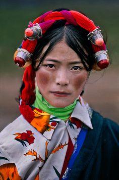 Asia | Portrait of a young Tibetan woman wearing a traditional headdress, Tagong, Kham, Tibet | © Steve McCurry  #beads #silver