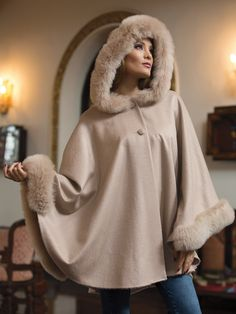 Annika When the weather changes and snowflakes fill the air with their sparkling beauty, this gorgeous hooded cape will keep you looking and feeling absolutely stunning. The silkiest 100% baby Alpaca wool is complemented by fluffy soft Alpaca fur around the hood and the hands. It fastens with two buttons near the collar, while two ingenious snaps inside the cape create a sleeve-like look around your wrists. Brought to you from Peru.