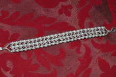 silver braclet with gray and burgundy