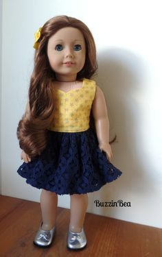 Yellow and navy floral peplum dress by BuzzinBea on Etsy. Made using the LJC Peplum Top pattern. Get it here http://www.pixiefaire.com/products/peplum-top-18-doll-clothes. #pixiefaire #libertyjane #peplumtop