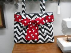 This tote bag is a beautiful Black and White CHEVRON with RED polka dot sash. The bag measures measures 17 1/2 inches wide and 13 1/2 inches tall and 5 inches deep. * I inserted a STRONG stabilizer on the bottom so the bag wont sag. * Snap closure. * 3 large pockets! * Padded cell phone pocket. (let me know the size of your cell phone upon ordering, otherwise the pocket will fit an iphone)  Perfect for the busy Mom.  Comfortable padded straps make this the perfect tote bag. CAN BE CUSTOM…