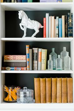 Create dramatic shelves with a dark wall and light pieces: http://www.stylemepretty.com/living/2016/11/15/a-coastal-inspired-living-space-for-a-family-of-four/ Photography: Caroline Lima - http://www.carolinelima.com/