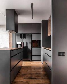 Nesta cozinha assinada pelo Metaforma, o tom escuro da marcenaria guiou a decoração sóbria e minimalista do espaço, enquanto os detalhes em madeira quebraram com a atmosfera monocromática e deram mais leveza ao espaço! Foto: Krzysztof Strazynski.