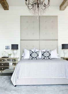 Bedroom with white beadboard walls and exposed beams. Love the tufted grey headboard.