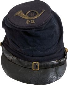 Union Model 1859 Forage Cap. Body of the cap is in fine condition with no damage, leather chinstrap is stiff and crazed, leather visor displays moderate crazing. Chin strap held fast with two matching federal eagle buttons. Crown displays what appears to be the original insignia for Company B, 22nd Infantry of an unknown Federal Infantry regiment.