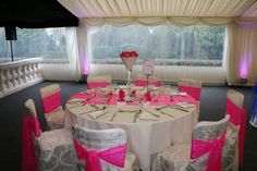 Shocking Pink Oraganza Sashes & Runner with Hot Pink Favour Boxes .   50cm Martini Glass Table Centre with White Stones, Candles & Pink Gerbera