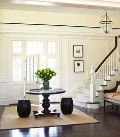 paneling , trim on top to separate first and second floor, center table, front door with window panes, sisal