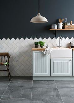 New ways to use tiles at home White metro kitchen tiles used as herringbone tiles against a navy wall with powder blue kitchen cupboards from RedOnline Blue Kitchen Cupboards, Kitchen Wall Tiles, Kitchen Flooring, Kitchen Backsplash, Backsplash Ideas, Tile Ideas, Metro Tiles Kitchen, Chevron Kitchen, Kitchen Feature Wall