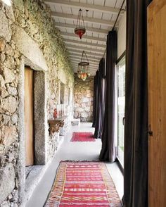 Exterior corridor with stone walls; woven rugs