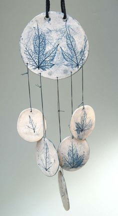Porcelain wind chime. Actual abutilon leaves were used to make the impressions on both sides of the porcelain chime pieces. The chime measures approximately 15 high + 15 synthetic cord; the colors are fired in and cannot fade. Nylon string and synthetic cord are used; can be hung inside or out-of-doors. Handmade in the US.  Was $29, now on sale for $14.