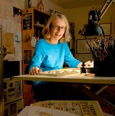 Roz Chast, New Yorker cartoonist, author, funny lady with a wicked wit. Here she sits at her desk with all the cool stuff of her studio.