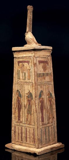 Egyptian Canopic chest. Three faces are painted, each with a goddess wearing a red tunic, alongside the god Anubis wearing a bodice and a loincloth; the fourth face is painted Anubis the jackal lying. It is closed by a lid surmounted by a figure wearing high akhem hawk feathers. Wooden polychrome stucco. Panels reattached. Egypt, Ptolemaic Period.