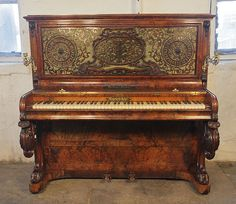 A Burling & Burling upright piano with a burr walnut case at Besbrode Pianos. Cabinet features an ornate fretwork front panel, moveable brass candlesticks and carved, cabriole legs. Piano has an eighty-five note keyboard and two pedals.