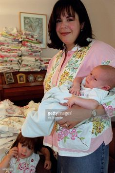 SO.0606.jackets.IS.1.Leeba Marks with her two youngest children at home. Marks, an Orthodox Jew and mother of 6, started a business making jackets out of antique fabrics and now her business is growing rapidly. She is wearing a jacket made from a vintage tablecloth. All her jackets utilize details from vintage tablecloths, napkins, tea towels and upholstery fabrics.
