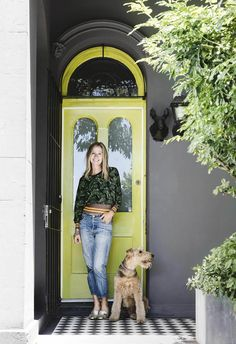 Victorian terrace facade with vibrant green front door and charcoal exterior. Chequered black and white tiles line the floor.