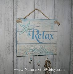 Relax Sign - Beach Décor - Starfish Décor - Beach Towel Hooks - Towel Holder - Tropical Décor - Wall Key Holder - Shabby Chic Beach Décor - Jewelry Holder This wooden sign and holder with the phrase, Relax is great tropical and coastal décor for your home. It was crafted from wooden pine planks, and any imperfections in the unique character of the three wooden planks add to the rustic appearance!! These planks are painted multi layers cream, aqua and shades of blue and adorned with a 5 resin…