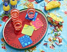 Cinco de Mayo Colorful Coasters  WHAT YOU'LL NEED: A few shades of acrylic paint; White paperboard coasters; Papel picado banner; Waterproof sealer