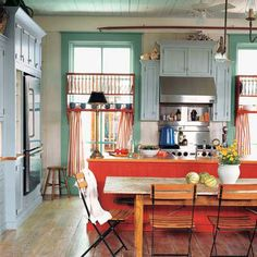 21 Favorite Cottage Kitchens-The kitchen offers more than a place to chop veggies or cook a roast. This colorful kitchen in Watercolor, Florida acts as the ultimate family gathering spot.