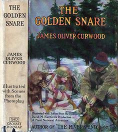The Golden Snare. James Oliver Curwood. New York: Grosset and Dunlap, 1921. Photoplay edition. Original dust jacket. With but two years of service in the RNMP Philip Raine finds himself somewhat unwillingly on the trail of Bram Johnson, wanted for murder and a wild, untamed and savage man who commands a pack of wolves as his brethren. But most peculiar of all is the Bram's golden snare intricately woven out of the finest, most delicate flaxen hair of a woman.