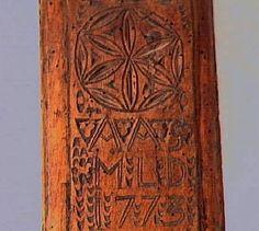 """Mangelbräde med skulpterat handtag. Karvsnittsdekor i form av tulpan, virvelhjul och rosettornament. Dessa ornament omgivna av nagelsnitt. Uddsnitt runt handtaget. Utmed långsidorna ristade dekorlinjer och uddsnitt.  Märkningen """"AAS MLD 1773"""", ristat på ovansidan."""