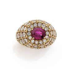 FRED  <br /> Bague dôme <br /> En or jaune 18k (750), sertie d'un rubis ovale dans un entourage et un rayonnement de diamants taillés en brillant <br /> Signée Fred Paris <br /> Tour de doigt: 52, Poids brut: 16.65 g <br />  <br /> A ruby, diamond and 18k yellow gold ring, by Fred