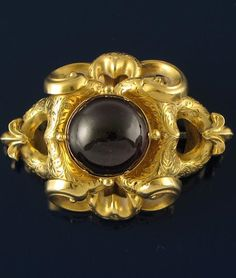 A Victorian gold scroll brooch, centred with a cabachon garnet. Glazed locket compartment to the reverse. ~ The garnet is named from the Latin for Pomegranate. because it resembles the seeds. It has been a talisman for thousands of years and is considered an apotropaic against melancholy.