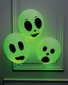 Glowing Ghost Balloons by Martha Stewart: Make them with green light sticks, white balloons and a marker for the faces! #Halloween #Martha_Stewart #Ghost_Ballooons