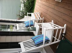 White rocking chairs on front porch with summer-perfect Sunbrella pillows and ombre lantern.