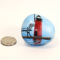 Highly detailed, miniature painting of the South Haven Michigan lighthouse on an ultra smooth beach stone. The South Haven lighthouse is one of the most popular and loved lighthouses found on the west side of Michigans coast line, and one of my own personal favorites! This small stone is painted with tiny brushes, several layers of high quality acrylic paints and coated several times with a durable varnish to provide years of enjoyment. Any white specks in the photos is glare from the…