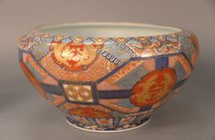 Imari fish bowl with three-claw dragon plaques, phoenix birds, and geometric designs, interior with grey coy.