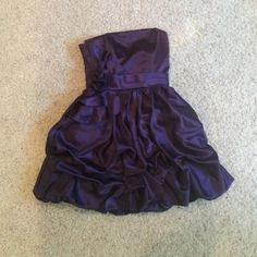 Jessica McClintock purple dress Originally $175 and completely unused!! Deep purple color, body hugging corset style top with  flower detail and ribbon waist divider, ruching detail on bottom. Would fit a size 0 or size 1. Perfect for bridesmaid / homecoming / prom/ event dress! Jessica McClintock Dresses