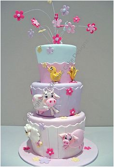 soft pastel farm animals on this three tier baby shower cake