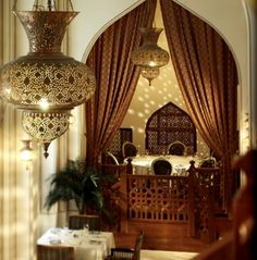 Gorgeous Moroccan inspired dining room including beautiful hanging lamps and a decorative screen.