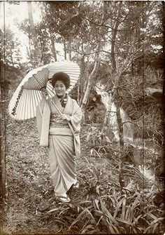 """Description: """"A summer shower in the woods, Miyanoshita, Japan (a girl walking through a wood with umbrella up)."""" Photograph taken by Herbert Ponting (1870-1935).  Date: c.1907   Our Catalogue Reference: COPY 1/507/154  This image is from the collections of The National Archives. Feel free to share it within the spirit of the Commons.  For high quality reproductions of any item from our collection please contact our image library."""