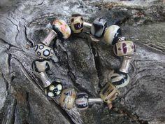Armband van zwart, ivoor en taupe, verwerkt aan dubbel siliconen elastiek