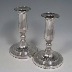 Antique Georgian sterling silver round-based candlesticks with panelled baluster columns, removable bobeches, and reeded bases. Made by John Green and Co., of Sheffield in 1800. Height 16 cms (6.25 inches), daimeter at base 10 cms (4 inches).