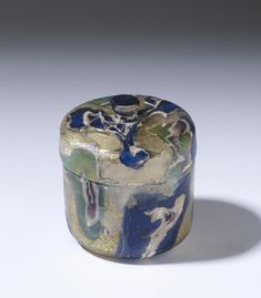Pyxis | Jerusalem, Israel (?) | Roman | glass, gold leaf | This pyxis, or cylindrical box, is an exquisite example of Roman luxury glassware, used to hold cosmetics or precious jewelry. Cylindrical in shape with a knob on the cover; stratified: green, white, yellow, blue