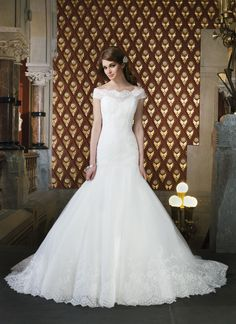 Justin Alexander wedding dresses style 8708 Alencon lace and tulle fit and flare features an off the shoulder  neckline and a drop waist. Gown features a hem lace and has a chapel  length train. Satin fabric buttons cover the back zipper.
