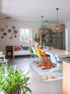 The large dining table was custom made. As is the cabinet filled with colorful tableware. The bamboo pendant lamps are from HKliving.