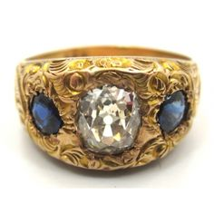 Victorian era 14 karat yellow gold, sapphire & Old Cut diamond 3-Stone engagement engagament ring with an intricate hand engarved design throughout featuring a 0.94 Carat Old Cushion Cut diamond flanked by 2 round cut natural blue sapphiresPrice Upon Request