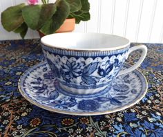 This is a 1950sblue and white Japanese cup and saucer in a pattern that reminds me of Blue Onion in blue transferware with gold trim. The porcelaincup is 2 in