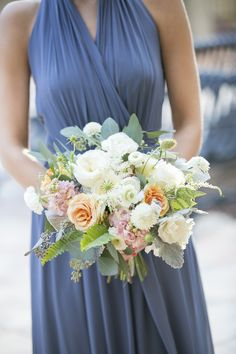 bridesmaid in a lovely french blue gown carries her loosley tied and organic bridesmaid bouquet of white patience garden rose, white ranunculus, vendela rose, white majolik spray rose, white scabiosa, dusty miller, fern, seeded eucalyptus, mondial rose, light peach rose & peach stock wrapped in cream satin ribbon.