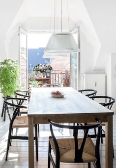 Bright and nordic dining space with a rustic wooden table and Wegners Y Chairs. We love the beautiful access to the balcony.