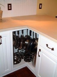 Don't have to buy an expensive lazy susan unit to effectively use the corner - just install hooks inside cabinets to hang pans, great idea!