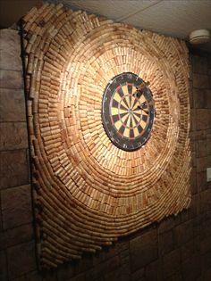 I just finished creating my dart board wall protection with wine bottle corks. Using a sheet of styrofoam, my husband cut it to the appropriate size and cut out the centre for the dart board. I used a hot glue gun to glue the corks to the styrofoam. I then used Welbond glue to ensure the corks stayed attached.